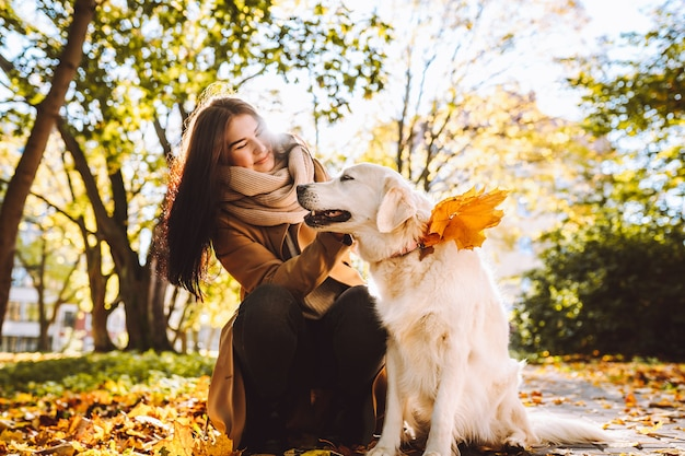 Femme marche et joue avec son golden retriever en automne park