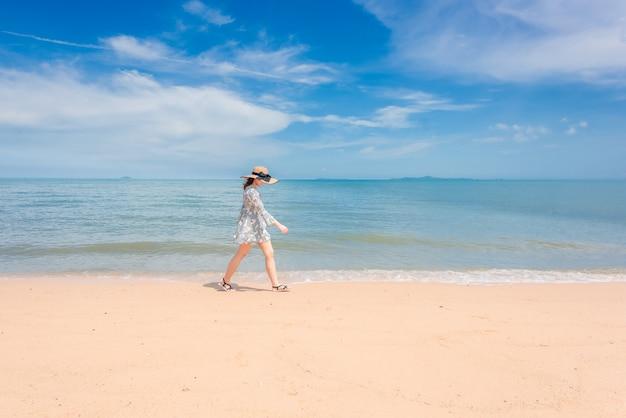La femme marche joyeusement sur la plage.
