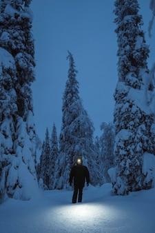 Femme marche avec une lampe frontale dans un parc national enneigé de riisitunturi, finlande