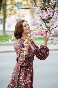 Une femme marche le long d'une rue printanière. la fille apprécie l'odeur d'un arbre en fleurs. belle femme vêtue d'une robe avec sakura cerise en fleurs