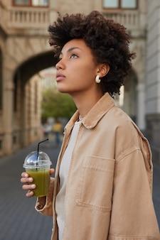 Une femme marche seule en ville boit un smoothie frais regarde au-dessus des promenades dans un lieu urbain vêtue d'une veste beige
