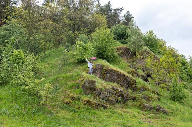 Une femme marche sous un parapluie dans les montagnes, parmi les rochers couverts de verdure