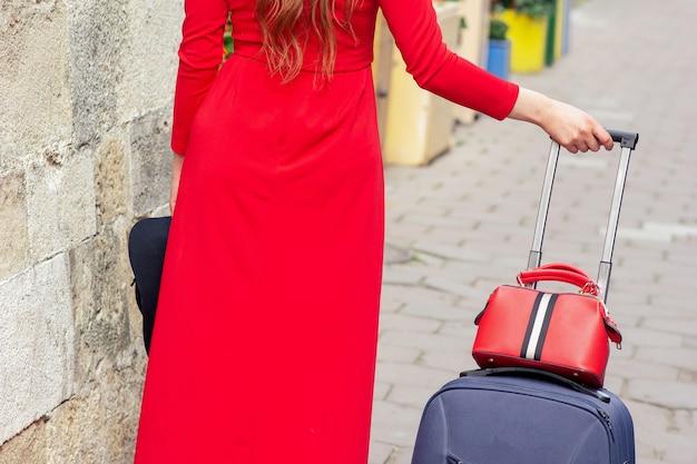 Une femme marche avec une valise en robe rouge dans la rue d'une ville