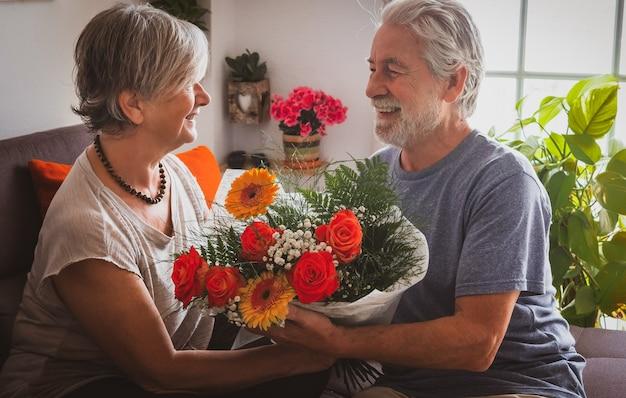 La femme et le mari célèbrent une saint-valentin romantique à la maison avec un grand bouquet de fleurs. deux personnes âgées amoureuses