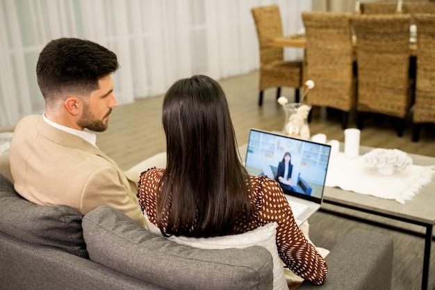 Femme et mari discutant de problèmes avec un psychologue familial par appel vidéo sur un ordinateur portable