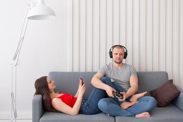 Femme et mari jouant à des jeux vidéo ensemble à la maison