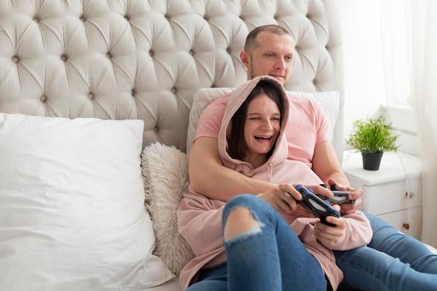 Femme et mari jouant à des jeux vidéo à la maison