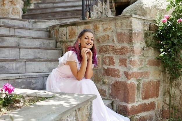 Femme mariée est assise sur les escaliers et attend son marié. femme aux cheveux violets dans une belle robe de mariée
