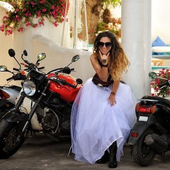 Femme mariée heureuse posant avec moto, mariage de motards, à l'extérieur