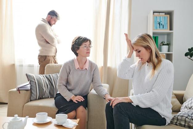 Femme mariée inquiète frappant son front tout en parlant à psyc