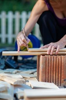 Femme marquant une ligne où couper une planche de bois dans un projet de bricolage de rénovation et d'amélioration.