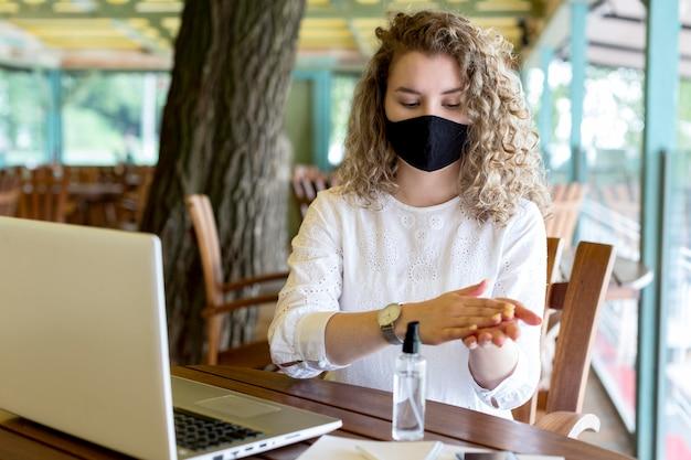 Femme avec masque à l'aide de désinfectant pour les mains