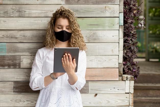 Femme avec masque à l'aide de tablette