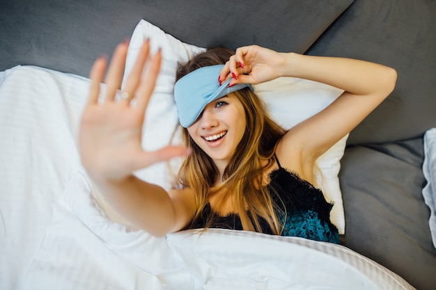 Une femme avec un masque aux yeux bandés pour dormir est allongée sur le lit le matin.