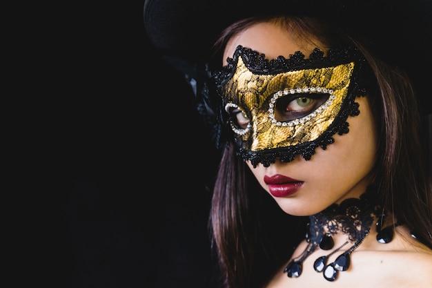 Femme avec un masque de carnaval sur un fond sombre