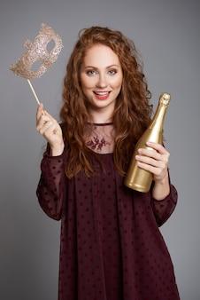 Femme avec masque et champagne