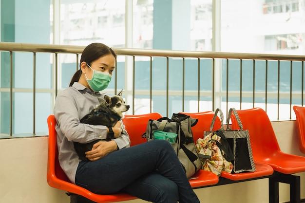 Femme en masque chirurgical protecteur tenant le concept de protection coronavirus chien.