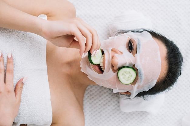 Femme avec un masque de concombre