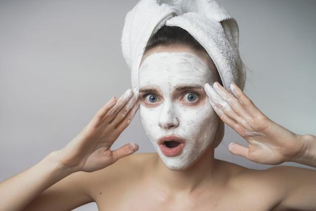 Une femme avec un masque cosmétique sur le visage, prend soin de la peau, avec une serviette sur la tête, après le bain. elle a mis ses mains à sa tête de surprise