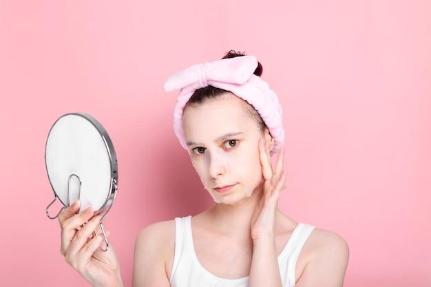 Femme avec masque cosmétique sur le visage, tient le miroir et touche le visage de la main sur fond rose
