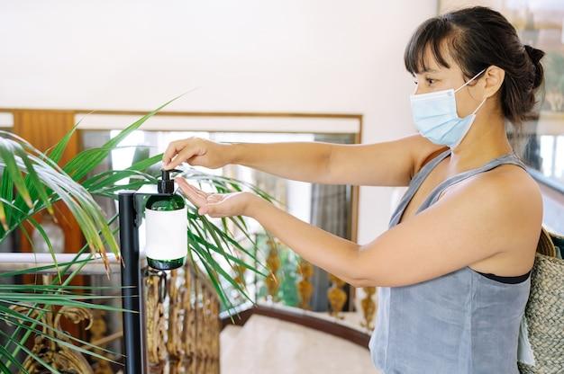 Femme avec un masque dans un hôtel mettant du gel désinfectant