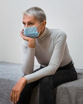 Femme avec masque facial en attente du médecin