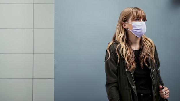 Femme avec un masque facial en public lors d'une épidémie de coronavirus