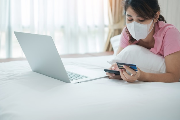 Femme avec masque facial tenant une carte de crédit et à l'aide d'un téléphone mobile et d'un ordinateur portable pour les achats en ligne sur le lit le matin à la maison.