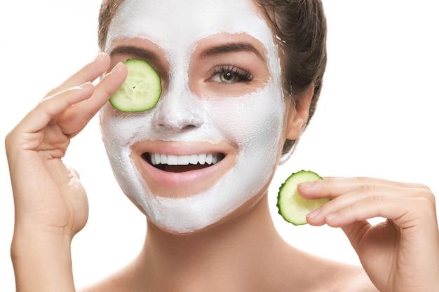 Femme avec masque facial et tranches de concombre dans ses mains