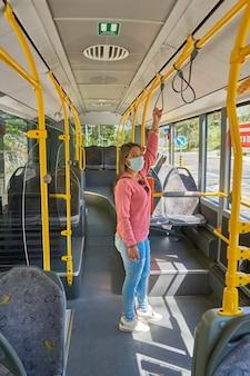Femme avec masque facial voyageant dans la ville dans le bus