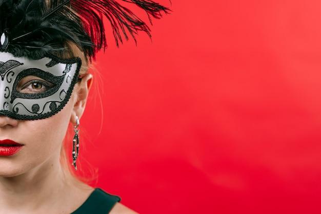 Femme, masque gris, plumes