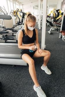 Femme avec masque médical à l'aide de désinfectant pour les mains à la salle de sport