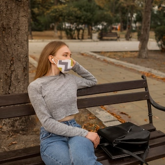 Femme avec masque médical assis sur un banc