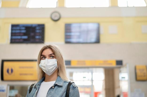 Femme avec masque médical à la gare publique