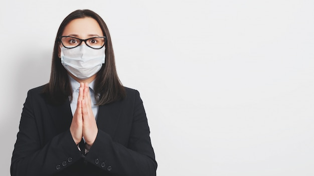 Femme en masque médical priant avec les mains jointes pour la fin de l'épidémie de coronavirus contre le gris