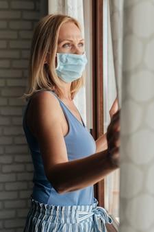 Femme avec masque médical regardant par la fenêtre pendant la quarantaine