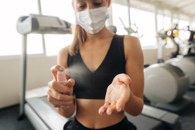 Femme avec masque médical à la salle de sport à l'aide de désinfectant pour les mains
