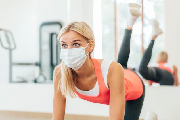 Femme avec masque médical travaillant à la salle de sport
