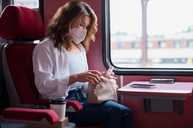 Femme avec masque médical utilisant un désinfectant pour les mains lors d'un voyage en train public
