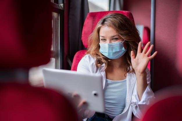 Femme avec masque médical utilisant une tablette pour un appel vidéo lors d'un voyage en train public