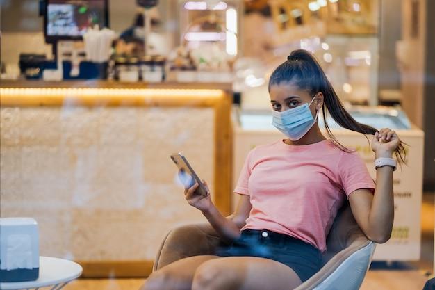 Femme avec masque médical visage à l'aide de smartphone au café.