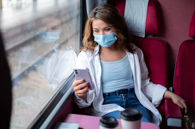 Femme avec masque médical voyageant en train public et utilisant un smartphone