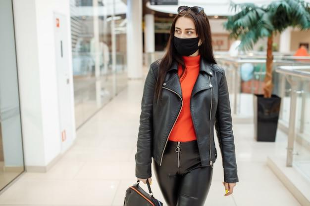 Femme avec un masque noir médical marche le long d'un centre commercial. pandémie de coronavirus. femme dans un masque de protection fait ses courses au centre commercial