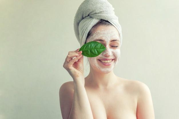 Femme avec masque nourrissant blanc ou crème sur le visage et feuille verte à la main, fond blanc