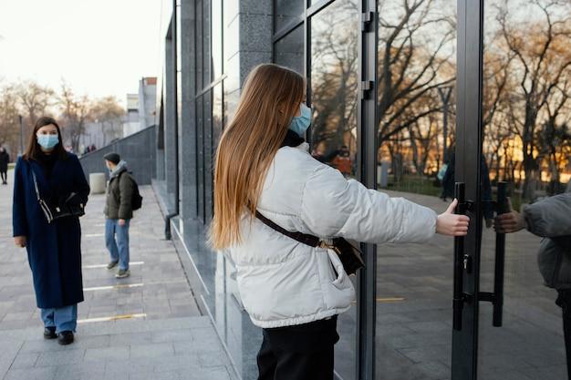 Femme avec masque ouvrant la porte