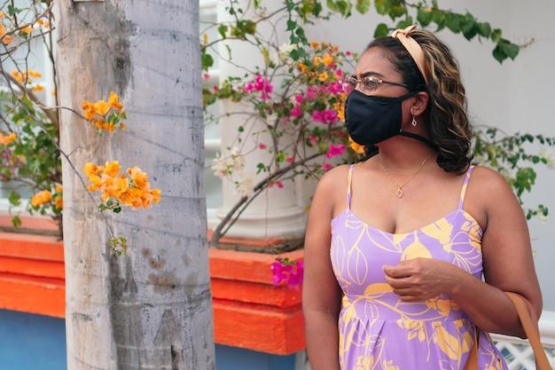 Femme avec un masque de protection antivirus et une robe d'été posant seule dans une rue