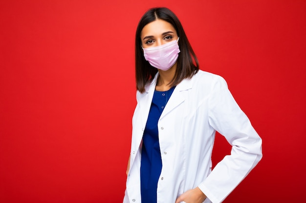 Femme en masque de protection contre les virus sur le visage contre le coronavirus et blouse blanche isolée sur le fond.