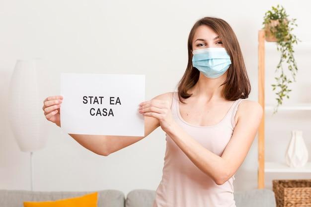 Femme avec masque et rester à la maison message