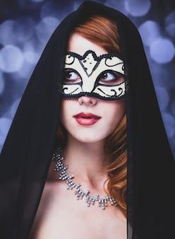 Femme en masque et robe noire sur fond gris avec bokeh