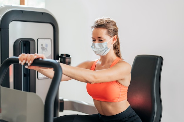 Femme avec masque travaillant dans la salle de sport